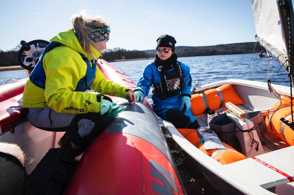 Seglaren Fia Fjelddahl sitter i en båt och ger instruktioner till en av sina adepter som sitter i en segelbåt.