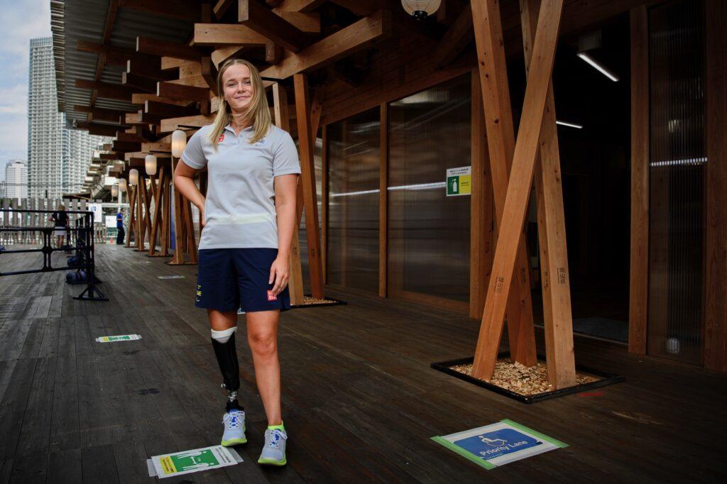 Lina Watz står med ena handen i sidan framför en träbyggnad på Paralympic plaza i Tokyo.